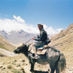 Jacob Baynham rides a yak in Afghanistan's Wakhan Corridor in 2006, an experience he would later write about for Wend Magazine. (Anna Elliot)